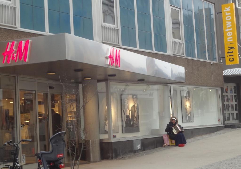 Kvinnlig tiggande dragspelare utanför H&M och City Network